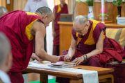 Его Святейшество Далай-лама подписывает фотографии с изображением Будды, чтобы преподнести их в качестве подарков буддистам из Вьетнама. Дхарамсала, Индия. 21 мая 2018 г. Фото: Тензин Чойджор.