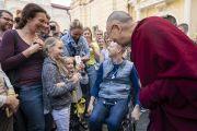 Покидая Вильнюсский университет по завершении публичной лекции, Его Святейшество Далай-лама останавливается, чтобы его сфотографировала маленькая девочка. Вильнюс, Литва. 13 июня 2018 г. Фото: Тензин Чойджор.