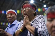 Надев ритуальные повязки, верующие слушают наставления Его Святейшества Далай-ламы в ходе посвящения Тысячерукого Авалокитешвары. Рига, Латвия. 18 июня 2018 г. Фото: Тензин Чойджор.
