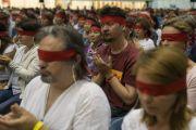 Надев ритуальные повязки, верующие слушают наставления Его Святейшества Далай-ламы во время заключительного дня трехдневных учений для стран Балтии и России. Рига, Латвия. 18 июня 2018 г. Фото: Тензин Чойджор.