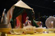 Вид на Его Святейшество Далай-ламу из-за подношений, стоящих на алтаре на сцене зала «Сконто». Рига, Латвия. 18 июня 2018 г. Фото: Тензин Чойджор.