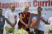 Его Святейшество Далай-лама держит свой портрет, преподнесенный ему по завершении церемонии запуска учебной программы «Счастье» для школ Дели. Нью-Дели, Индия. 2 июля 2018 г. Фото: Тензин Чойджор.