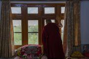 Его Святейшество Далай-лама смотрит из окна своей резиденции на площадку для проведения учений, где собрались местные жители, чтобы поприветствовать своего духовного лидера. Занскар, штат Джамму и Кашмир, Индия. 21 июля 2018 г. Фото: Тензин Чойджор.