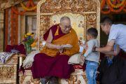 Его Святейшество Далай-лама угощает сладостями маленького мальчика во время церемонии закладки первого камня библиотеки и учебного центра в монастыре Тикси. Ле, Ладак, штат Джамму и Кашмир, Индия. 29 июля 2018 г. Фото: Тензин Чойджор.