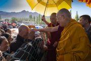 Направляясь из своей резиденции на площадку для проведения учений Шевацель, Его Святейшество Далай-лама шутливо приветствует верующих. Ле, Ладак, штат Джамму и Кашмир, Индия. 31 июля 2018 г. Фото: Тензин Чойджор.