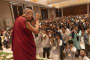 Поднявшись на сцену в начале лекции, организованной по просьбе общества «Видьялоке», Его Святейшество Далай-лама приветствует слушателей. Бангалор, штат Карнатака, Индия. 12 августа 2018 г. Фото: Тензин Чойджор.