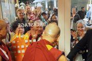 Направляясь на сцену концертного зала Мальмё, Его Святейшество Далай-лама приветствует верующих, собравшихся у дверей, ведущих за кулисы. Мальмё, Швеция. 12 сентября 2018 г. Фото: Джереми Рассел.