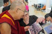По завершении встречи одна из членов групп поддержки Тибета показывает Его Святейшеству Далай-ламе старые фотографии, сделанные в Тибете. Мальмё, Швеция. 13 сентября 2018 г. Фото: Джереми Рассел.