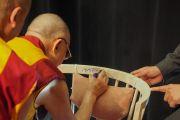 По завершении публичной лекции в университете Мальмё Его Святейшество Далай-лама оставляет надпись на стуле «Буддийский монах Далай-лама». Мальмё, Швеция. 13 сентября 2018 г. Фото: Джереми Рассел.